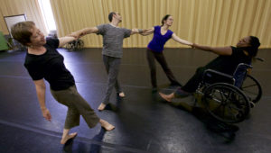 Four adults of different ages, ethnicities and abilities, including a person in a wheelchair are connected by their hands dancing in a line. They are in a dance studio.
