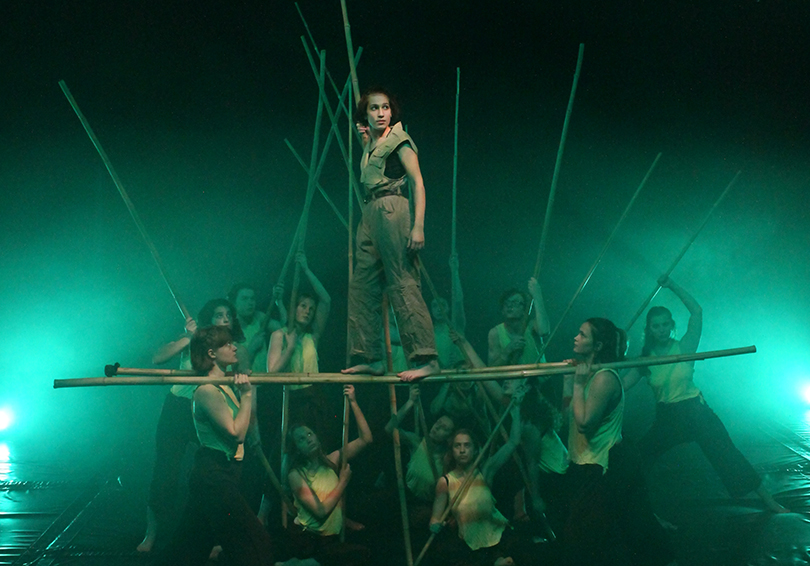 Photo is of a group of teens looking intently at one teen balanced on top of two bamboo poles. The background is green and murky.